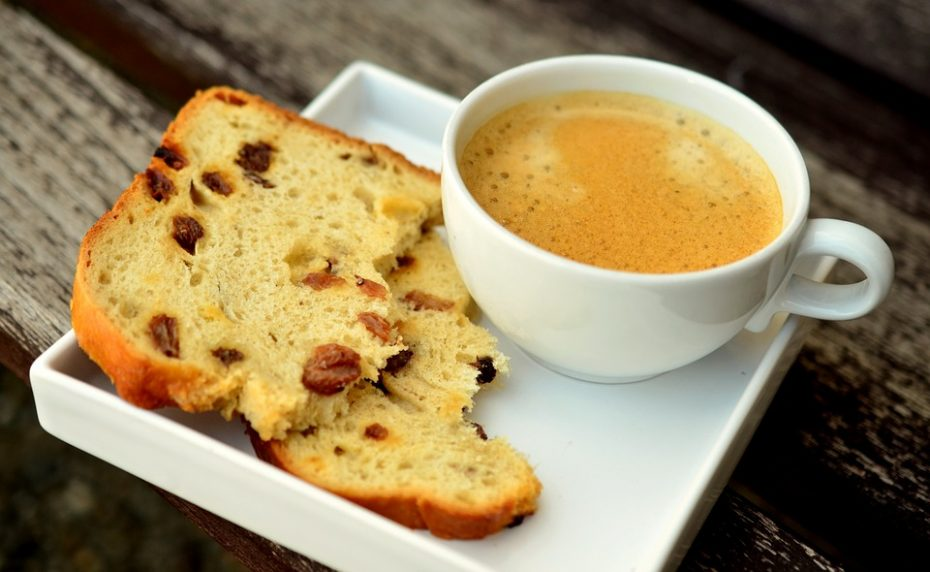 Fruit loaf and a cup of coffee sat on a small white tray.