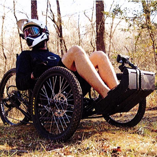 A man wearing a helmet is sitting in a forest on an adapted bike.