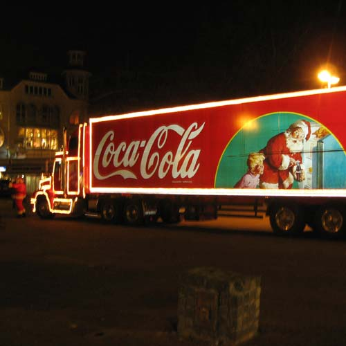 A red truck with Coca-Cola truck with a picture of Santa on the side.