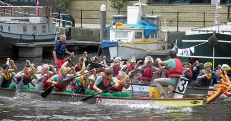 People are in boats with their faces painted, taking part in a race at the Leeds waterfront festival.