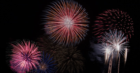 A firework shoots bright colours across the dark night sky
