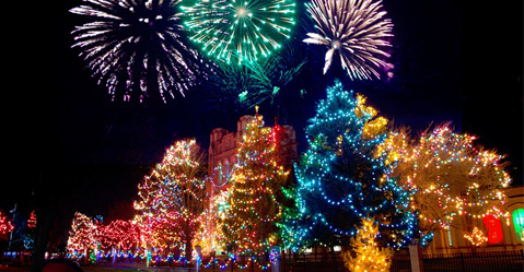 3 Christmas trees are decorated with chrismas decorations and lit with lots of bright christmas lights. In the sky above the christmas trees is a fireworks display.