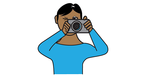 A person is holding up a camera to his eye and looking through the view finder