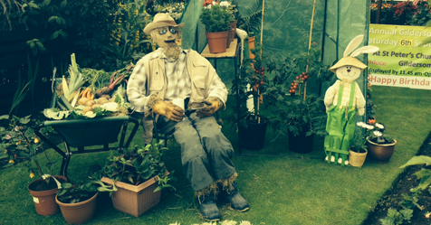 A scarecrow in a garden is sat on a chair next to some flowers.